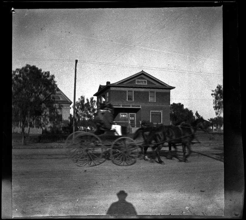 Horse-drawn carriage passes in front of the West's house, Los Angeles, about 1898