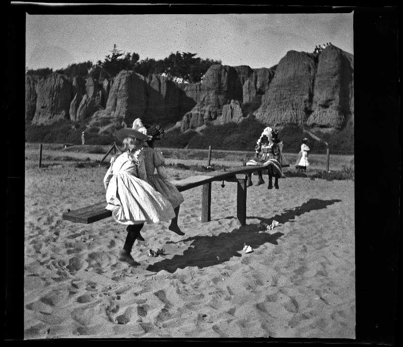 Girls play on a seesaw on the beach, Santa Monica, about 1895