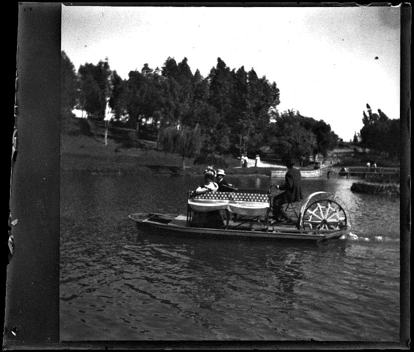 Man steers a bicycle boat with passengers on the lake at Hollenbeck Park, Los Angeles, about 1898