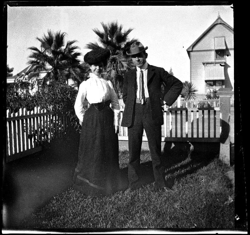 H. H. West and Mertie Whitaker stand in the Whitaker's front yard, Los Angeles, about 1898