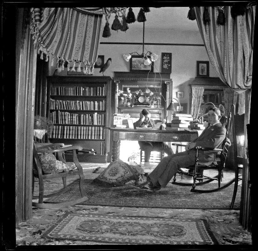 Wayne West and Wilson West sit in the library of the West's house, Los Angeles, about 1900