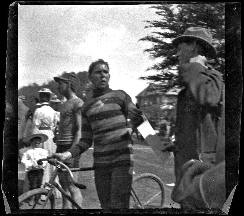 Guy West holds his bike while speaking to another man, Los Angeles, about 1900