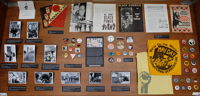 Exhibit case featuring material from the Steve Louie Asian American Movement Collection, the Cheryl Nassar papers, the Underground, Alternative and Extremist Literature collection, the Carol Waymire collection of periodicals and ephemera, and the LA Times photographic archive.