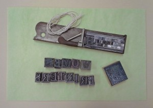 Printer's ornaments, a composing stick with type and spacers, and string used for tying blocks of type. These items were borrowed from the Information Studies department's letterpress lab.
