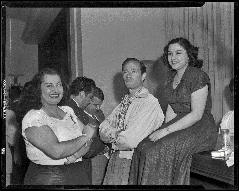 Mel Ferrer, actor, with director Robert Rossen (in background) and fellow attendees of a party for The Brave Bulls, circa 1950-1951