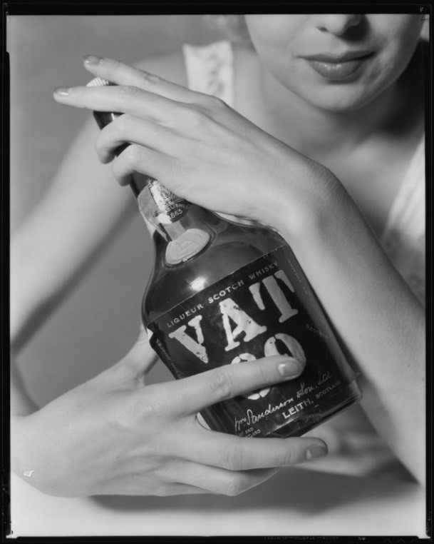 Allyn Drake, actress, posing with a bottle of Vat 69 scotch, circa 1934-1935