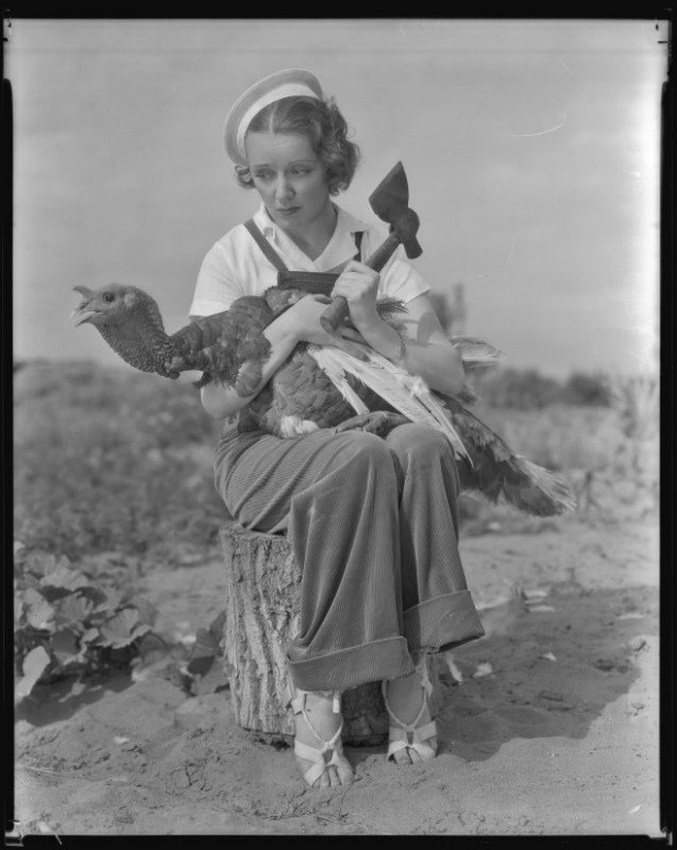 Inez Courtney, actress, holding a hatchet and a turkey, circa 1934-1939