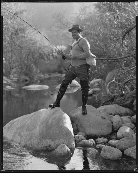 Jack Holt, actor, fishing in a stream, perhaps for a Silver Screen magazine feature, 1927-1939