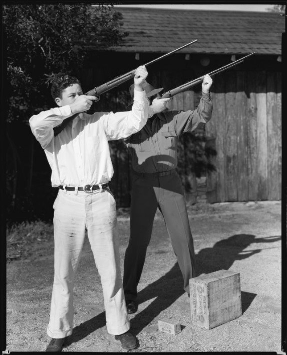 Tim Holt and his father Jack Holt, actor, aiming rifles, probably in their yard, Santa Monica, circa 1934