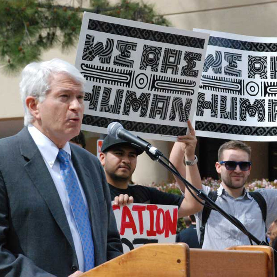 "A speaker at a podium, with demonstrators behind carrying signs saying ""We Are Human"""