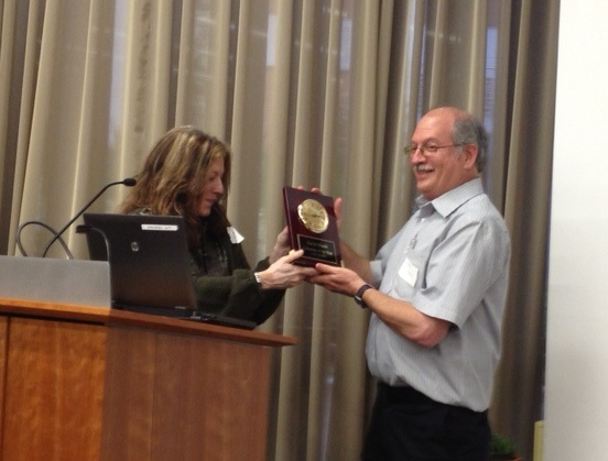 Angela Riggio handing off Librarian of the Year prize (clock with name plate) to David Hirsch.