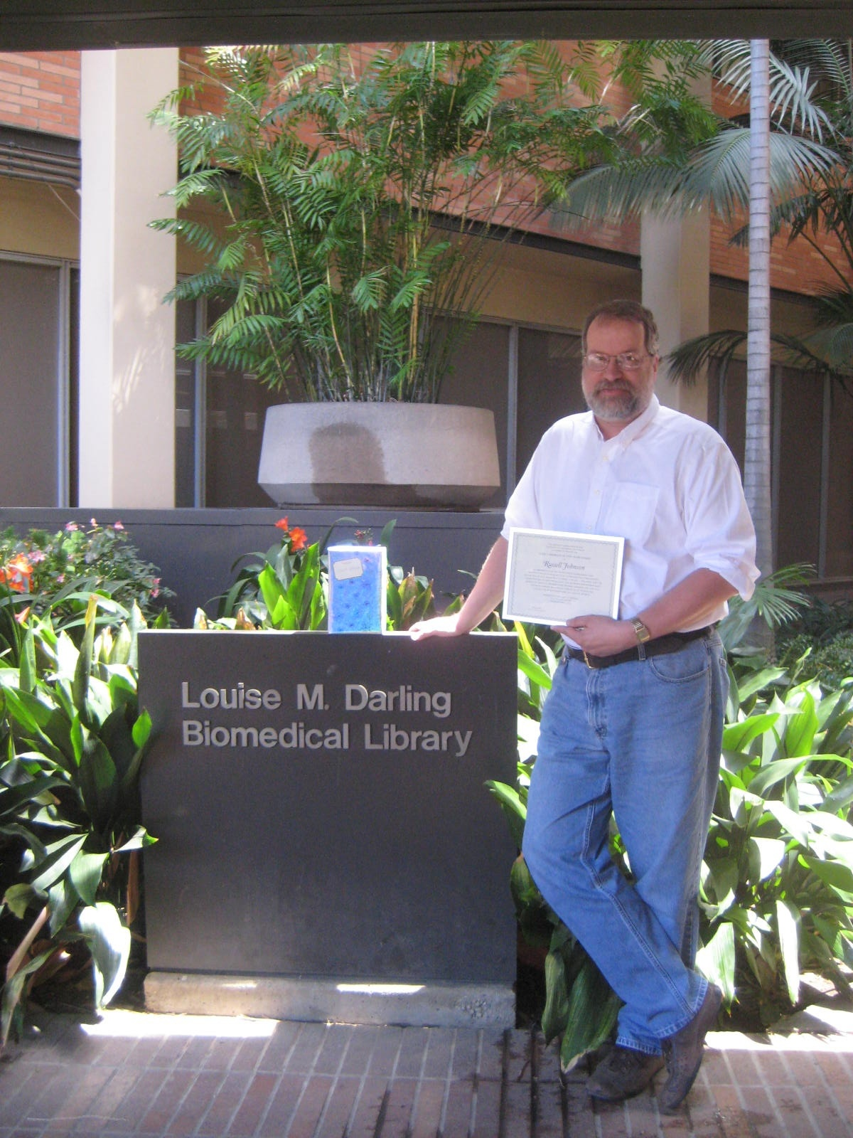 Russel Johnson holding certificate by the Louise M. Darling Biomedical Library sign.