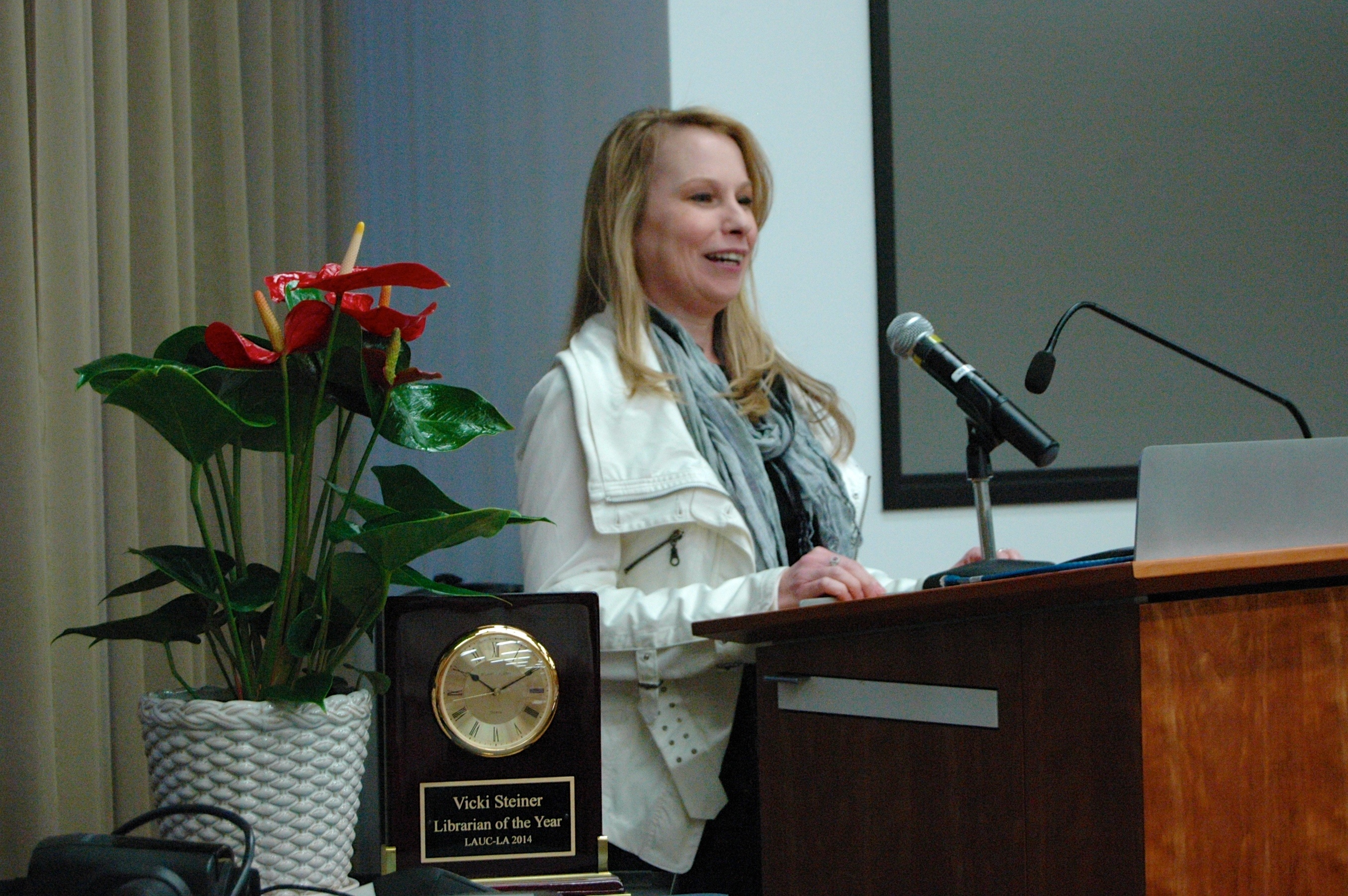 Vicki Steiner at the podium delivering acceptance speech; Librarian of the Year prize (clock) with flowers to the left.