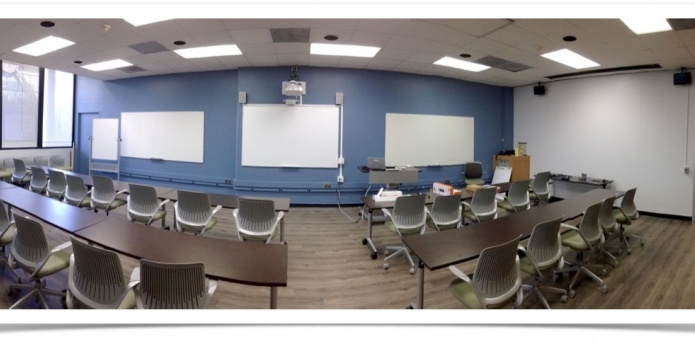 Wide shot of classroom showing blue walls, whiteboards, tables and chairs