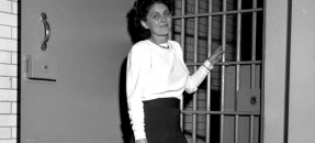 Communist Party leader Dorothy Healey standing before jail cell in Los Angeles, Calif., 1949