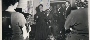Black and white photo of Diplomat Ralph J. Bunche being feted at local activist Bea DeVaughn's house, Los Angeles, 1949