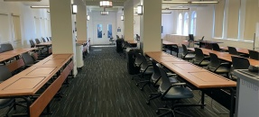 interior of classroom with long rows of desks and chairs