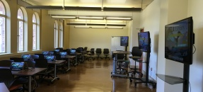 Image of entire classroom including monitors and tables