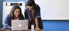 Two student workers in CLICC shirt looking at laptop while in a lab or classroom