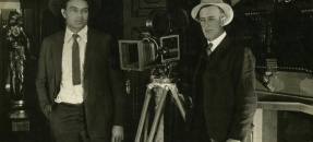 Noble Johnson standing with Harry Gant next to motion picture camera.
