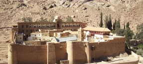 Photo of St. Catherine's monastery, showing ancient walls and surrounding hills.