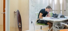 Student sitting alone in study room with skateboard propped against wall