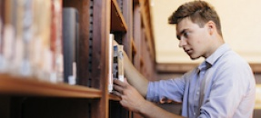Student looking at books in a library