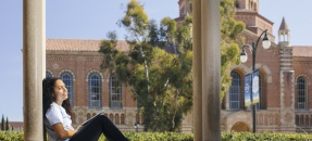 Student with UCLa Powell Library in the background