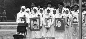 Arab men and women, dressed in all white, wearing pictures of objectors during demonstration against Iran's Ruhollah Khomeini in Los Angeles, Calif., 1985