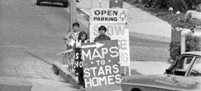 "Three boys standing on street corner with ""Maps To Stars Homes"" placards in Los Angeles, Calif., 1973"