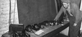 Detective B.J. Anderson examining table laden with telephones at raid on bookie at 923 S. San Julian in Los Angeles, Calif., 1938